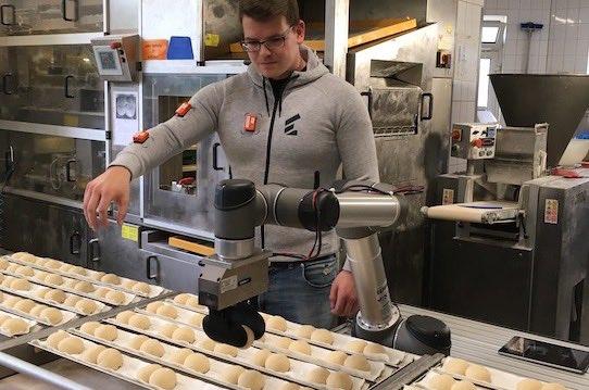 """Wandelbots-Mitarbeiter Gunther Mielke führt vor, wie der Roboter in der Backstube """"angelernt"""" wird. Foto: Stephan Hoenigschmid"""