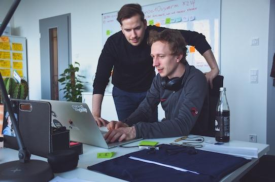 Mitgründer Philipp Dienst und Jakob Blume (v.l.n.r.) tüffteln an der nächsten Coding-Challenge, bei der Entwickler Unternehmen anonym zeigen können, was sie drauf haben. Foto: Felix Hanspach/Entwicklerheld